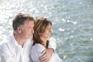 Mature couple looking away with water background