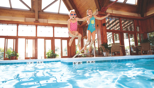 kids jumping into indoor pool