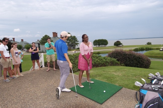 Lady Taking Swing with Instructor Giving Advice and Spectators Watching