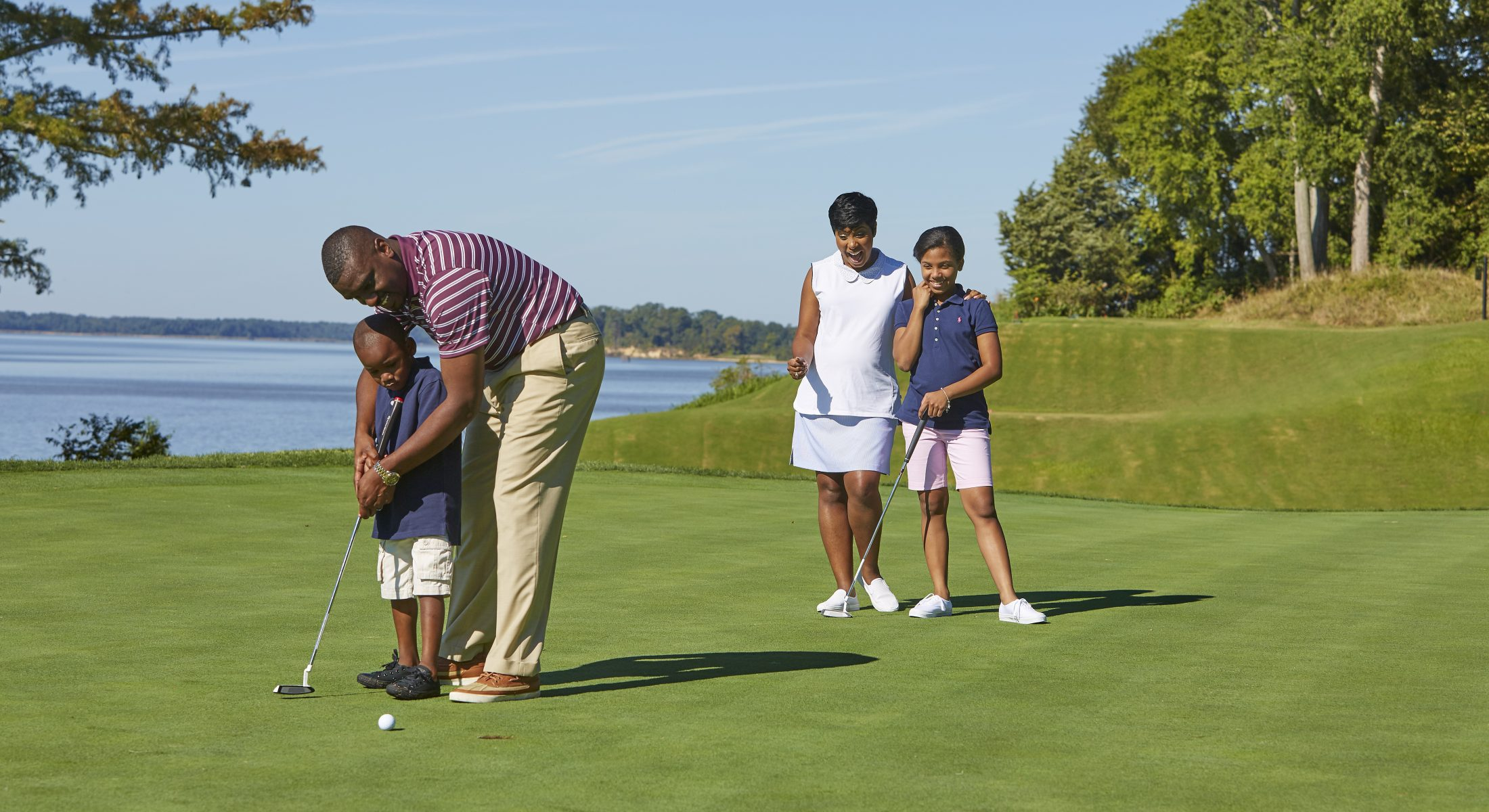 Father Teaching Son to Golf With Mother and Daughter Watching